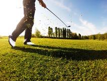 高尔夫球运动员执行从航路的一次高尔夫球球击。 免版税库存图片