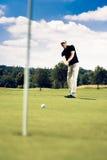 高尔夫球运动员投入 免版税库存照片