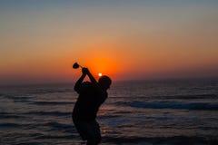 高尔夫球运动员摇摆的日出海洋  图库摄影