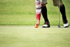 高尔夫球运动员标记他的位置球 免版税库存照片