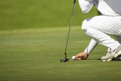 高尔夫球运动员标记他的在绿色的位置 免版税库存图片
