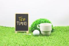 高尔夫球运动员的茶时间、标志和咖啡杯和高尔夫球在绿草 免版税图库摄影