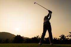 高尔夫球运动员行动,当日落时 库存照片