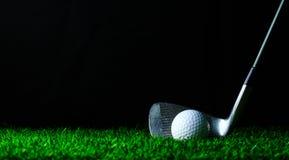 高尔夫球铁和高尔夫球在绿草 免版税库存图片