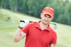 高尔夫球领域的高尔夫球运动员与俱乐部 免版税库存图片