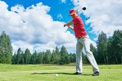 高尔夫球领域的高尔夫球运动员与俱乐部 免版税图库摄影