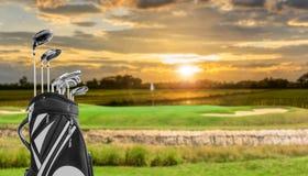 高尔夫用品和高尔夫球袋在绿色和孔作为背景 免版税库存图片