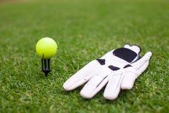高尔夫用品:球和手套在绿草 免版税库存图片