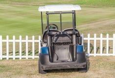 高尔夫车在白色木篱芭附近的绿色高尔夫球场公园 免版税图库摄影