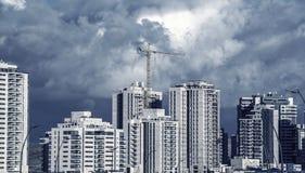 高层塔吊和新的居民住房的蓝色被定调子的图象 库存照片