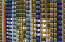 高层居民住房的墙壁与红色和蓝色和燃烧Windows,大大都会的公寓的 库存照片