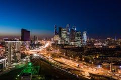 高层建筑物和运输大都会、交通和汽车模糊的光在多车道的高速公路和公路交叉点的 库存图片