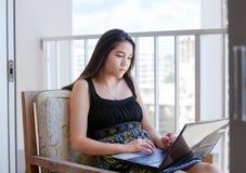 高层露台的两种人种的青少年的女孩有便携式计算机的 免版税库存图片