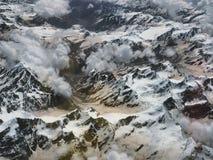 高山冰川:峰顶白色冰的永恒舌头下降入在透明积云clou中的多雪的谷 免版税库存图片