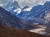 高山冰河谷在喜马拉雅山:用雪报道的一个巨大的峰顶,在峰顶的塔,河沿bott流动 图库摄影