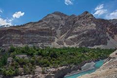 高山印度河,绿松石河的谷传送带,巨大的峰顶,在河床树附近 库存图片