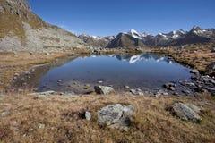 高山反射:一个小高山湖在意大利阿尔卑斯;它的晚秋天,没有人 免版税库存图片