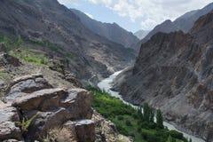 高山是印度河峡谷,沿河床的峭壁,绿色植被,在前景的巨大的冰砾 免版税图库摄影