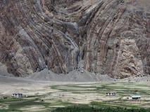 高山村庄:一个巨大的多彩多姿的岩石在领域和小屋,在美丽的岩石中的巨大的空间上耸立 免版税库存照片