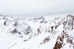 高山横向 在雪的高山在多云天 库存照片