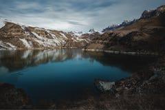 高山湖在北高加索,包围由史诗岩石和明亮的冬天满天星斗的天空在日出 免版税库存图片