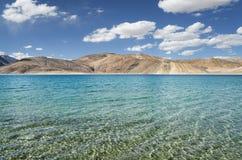 高山湖透明水和沙漠小山  库存照片