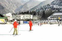 高山滑雪学校 辅导员和学生五颜六色的滑雪设备的 图库摄影