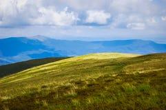 高山牧场地在一多云天 免版税库存照片