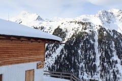 高山瑞士山中的牧人小屋房子和山全景有雪的在冬天在Stubai阿尔卑斯 免版税图库摄影