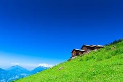 高山瑞士山中的牧人小屋绿色山坡 库存图片