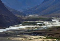 高山的河床:流动在沙丘、小绿色领域和黑暗中的高银行中的水小河 库存照片