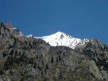 高山解冻 在春天的白色峰顶 免版税库存照片