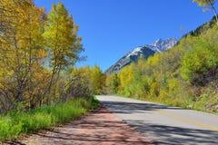 高山路通过与五颜六色的白杨木的山在叶子季节期间 免版税库存图片