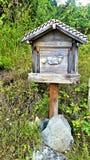 高山邮箱,与母牛雕刻的被风化的灰色木头 库存图片