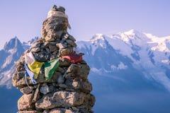 高度在偶象勃朗峰锡前面的石标和西藏人旗子 免版税图库摄影