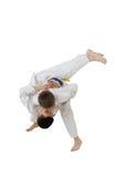 高投掷柔道训练白色和服的男孩 免版税库存照片