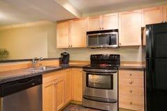 高效率,紧凑厨房设计用蜂蜜弄脏了厨柜 免版税库存照片