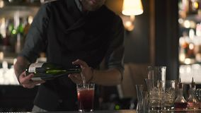 高有胡子的在玻璃的侍酒者倾吐的酒与冰 做在现代酒吧身分的男服务员鸡尾酒在柜台附近 股票视频