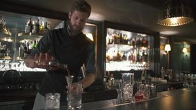 高有胡子的在金属瓶子的侍酒者倾吐的兰姆酒,然后在玻璃 做在现代酒吧的男服务员鸡尾酒与许多 股票视频