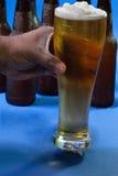 高杯啤酒在手中 免版税库存图片