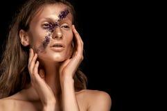 高档时尚神色、特写镜头妇女秀丽画象有明亮的构成的与与金嘴唇的金皮肤和横跨面孔的紫色条纹 图库摄影
