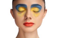 高档时尚神色、特写镜头秀丽画象、明亮的构成与完善的干净的皮肤与五颜六色的红色嘴唇和蓝色黄色眼影膏 免版税库存照片