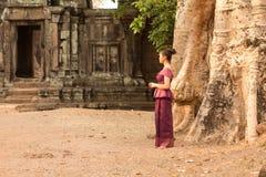 高棉礼服的柬埔寨女孩由一个古老门和树在吴哥城 库存照片