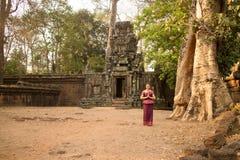 高棉礼服的柬埔寨女孩由古老墙壁和树在吴哥城,吴哥市 免版税库存照片