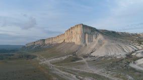 高灰色山峭壁和绿色低地的美好的平衡的看法在乡下路附近反对天空蔚蓝 ?? 股票视频