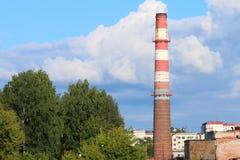 高烟囱管子在绿色树中的现代植物在城市 库存照片