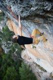 登高的攀岩运动员富挑战性峭壁 极端体育climbi 免版税库存图片