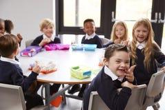 高的观点的一起坐在圆桌上的小学孩子吃他们的被包装的午餐,面对Th的一些转过来 库存照片