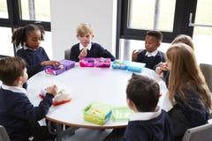 高的观点的一起坐在圆桌上的小学孩子吃他们的被包装的午餐 库存图片