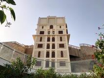 高石方形大厦、一个塔与被雕刻的窗口对一个石墙,岩石和树与绿色叶子在热带Ar 免版税库存照片